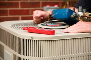 technicians hands with tools on top of ac outside unit