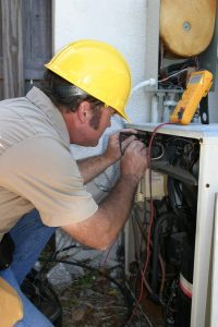 male technician doing service on an hvac system