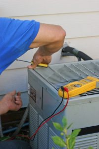 technician working on the outdoor unit of an air conditioner