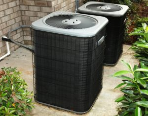 Two outdoor ac units sitting on concrete