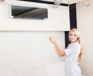 Female-holding-remote-control-air-conditioner