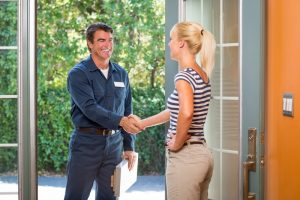 Repairman-in-uniform-and-clipboard-greeting-a-housewife-at-the-front-door.