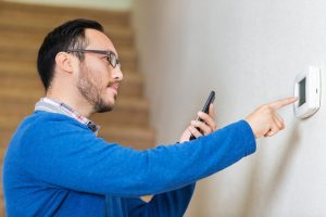 man-adjusting-thermostat