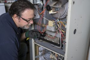 technician-looking-at-inside-of-furnace