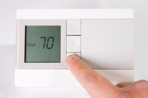 hand-adjusting-digital-thermostat