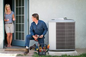 air-conditioning-technician-speaking-to-homeowner-while-working