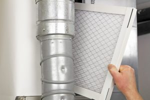 homeowner-putting-clean-air-filter-in