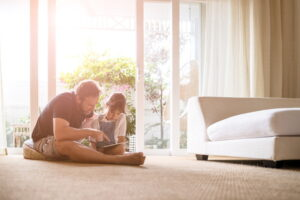 dad-and-daughter-sitting-in-living-room-with-sun-shining-in